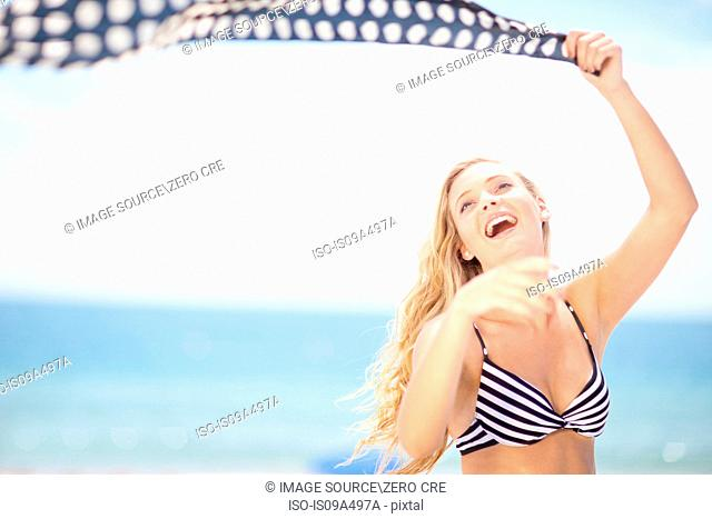 Woman playing with scarf on beach