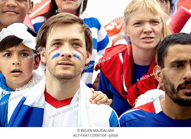 French football fans watching match attentively