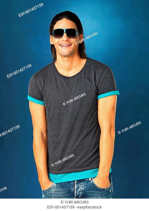 Handsome man with hands in pocket and wearing sunglasses