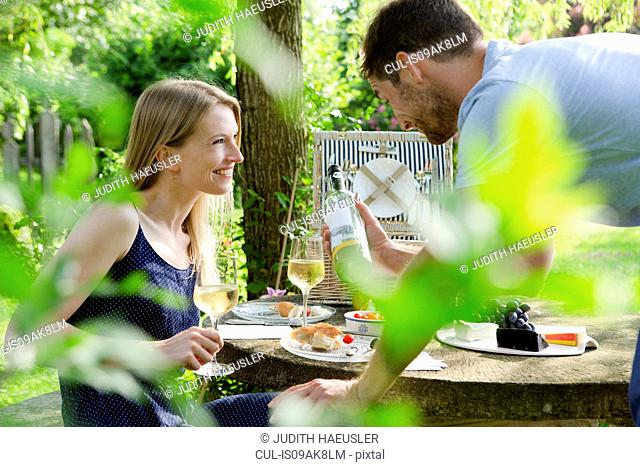 Mid adult couple having picnic with white wine in garden