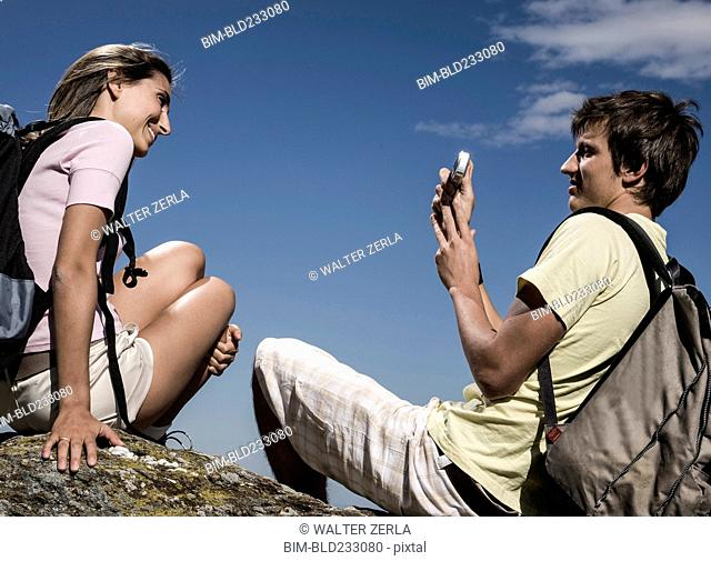 Man photographing woman on rock with cell phone