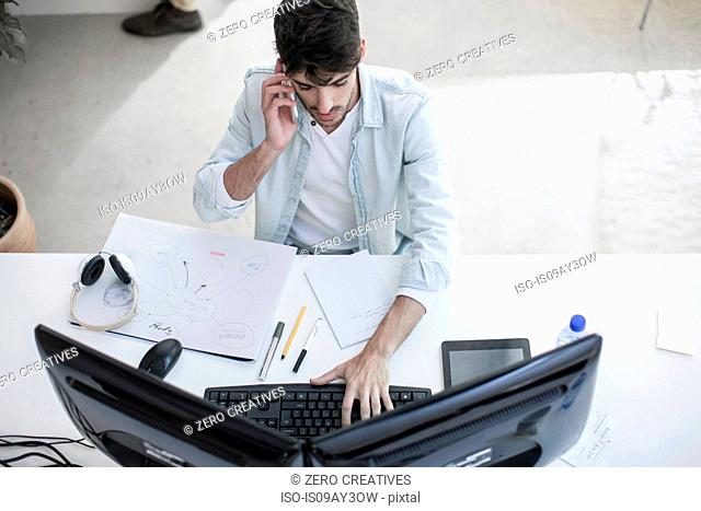 Overhead view of male designer talking on smartphone whilst typing in design studio