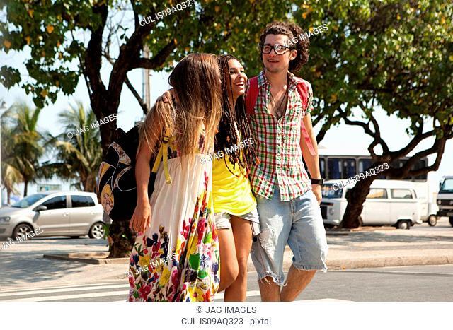 Three young adult friends strolling on sidewalk, Copacabana, Rio De Janeiro, Brazil