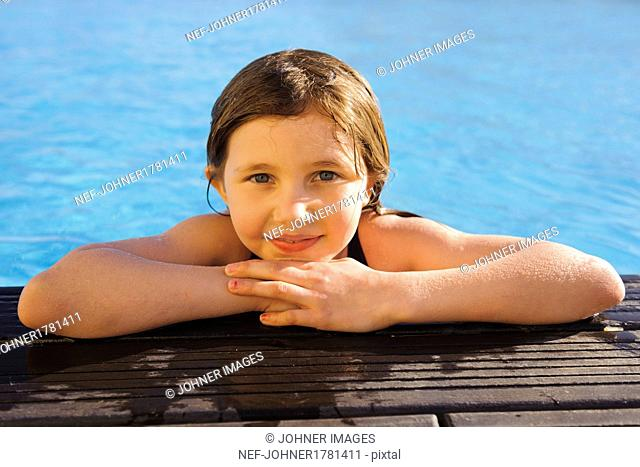 Portrait of girl on edge of swimming-pool