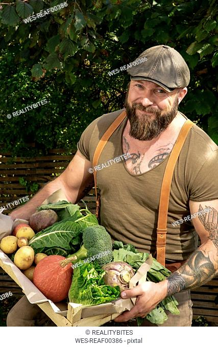 Mature man carrying crate with vegetables in his garden