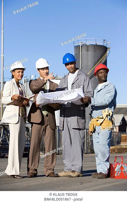 Multi-ethnic businesspeople and construction workers looking at blueprints