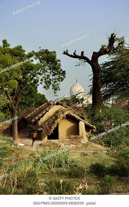 Mud huts with mausoleum in the background, Taj Mahal, Agra, Uttar Pradesh, India