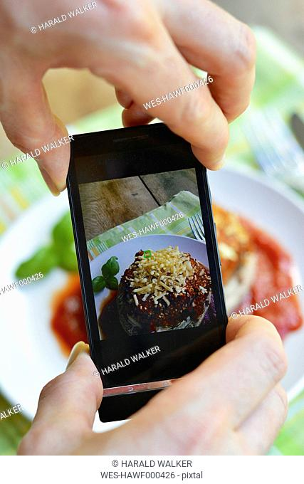 Man taking a photo of a dish, Stuffed Portobello Mushrooms, with a smart phone
