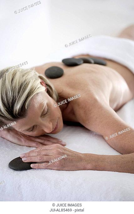 Senior woman getting spa stone treatment