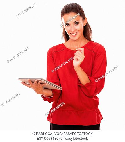 Portrait of pretty hispanic woman working on her tablet pc while standing and smiling at you on isolated studio