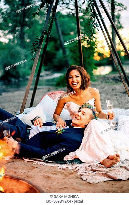 Bride and groom reclining by campfire on lakeside