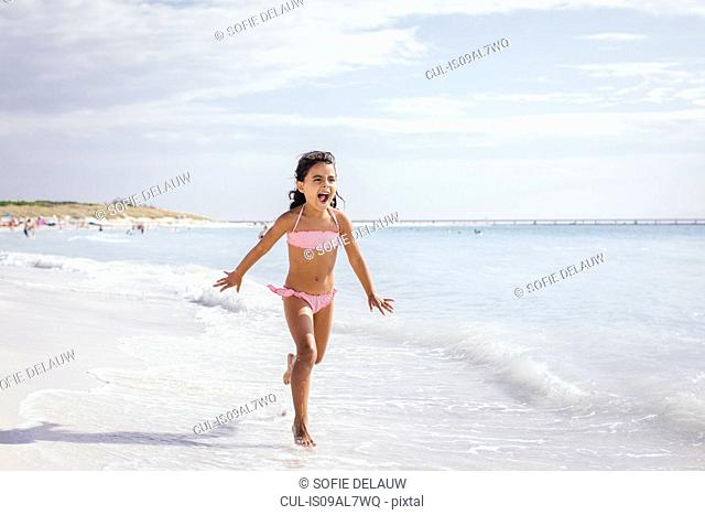 Girl running on beach, Tuscany, Italy