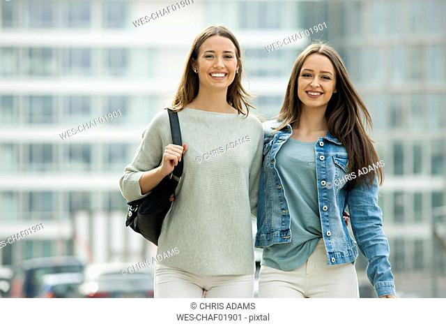 Two girlfriends walking in the city with arms around