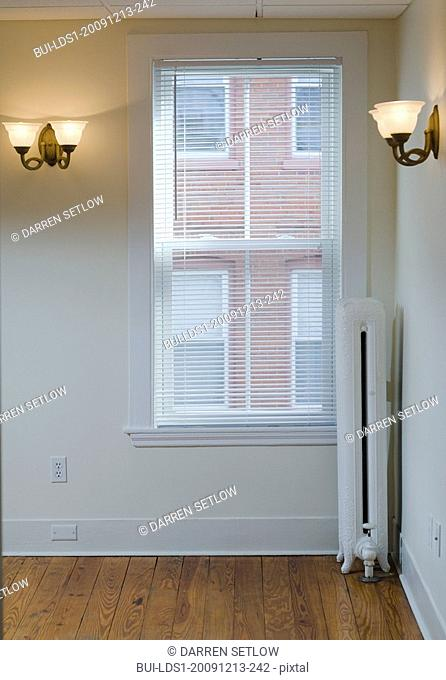 Empty room in apartment with hardwood floor and heater