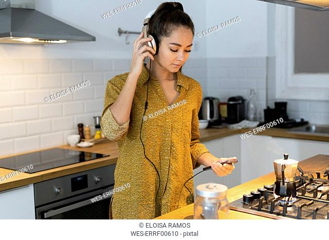 Young woman listening musuc in the kitchen, while preparing her morning coffee