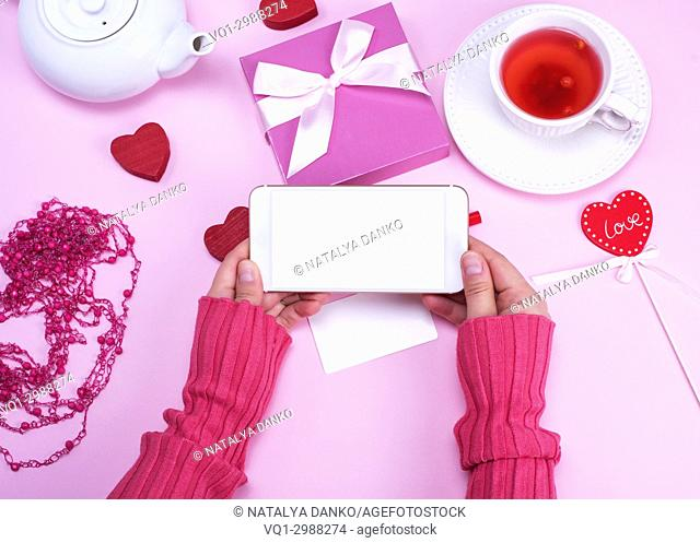 two female hands holding a smartphone with an empty white screen on a pink table background with a cup of tea and a box with a bow, top view