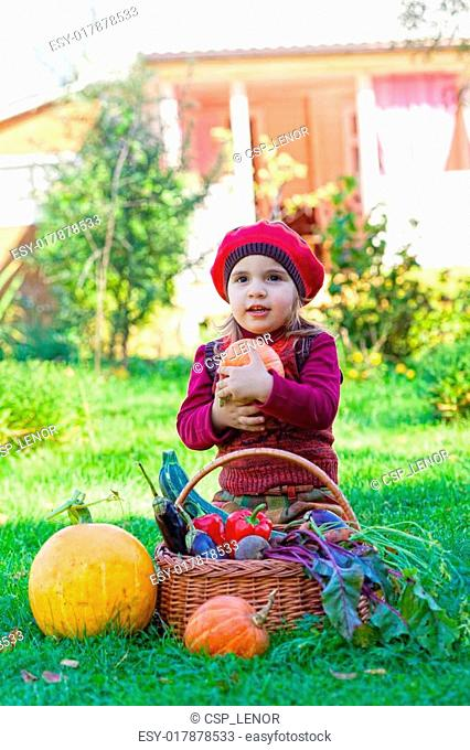 little girl sits on a grass and holds a pumpkin