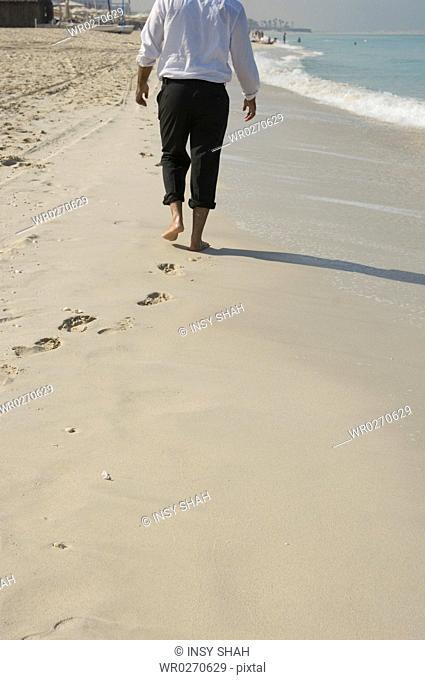 Businessman walking on the beach in formal wear