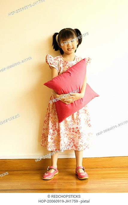 Portrait of a girl smiling and holding a pillow
