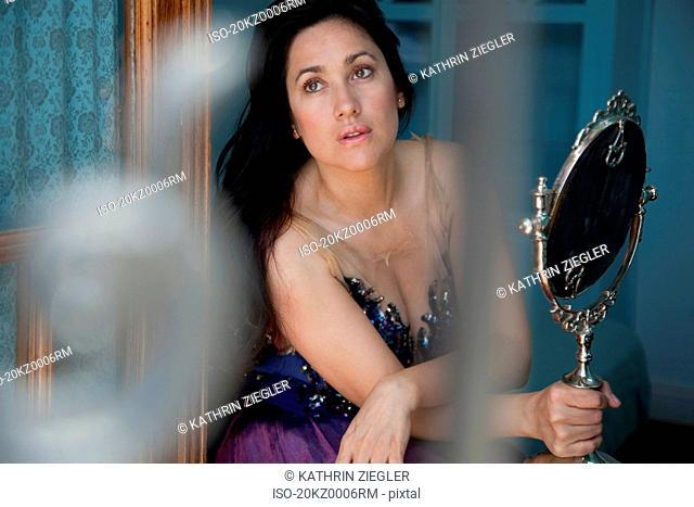 Woman holding mirror, looking away