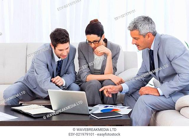 Business people using laptop and working together on sofa