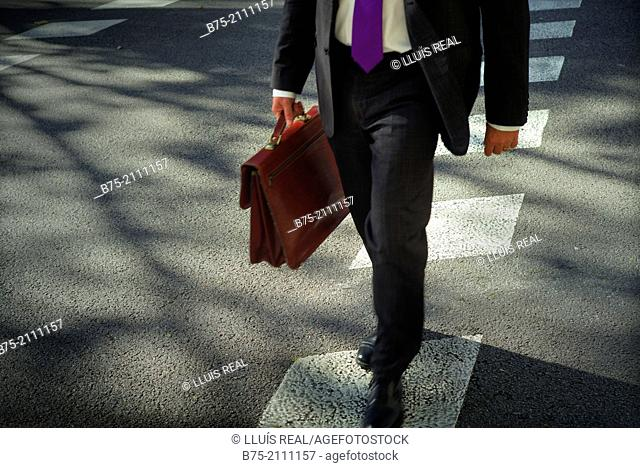 Executive with portfolio crossing a street in Barcelona. Spain, Europe