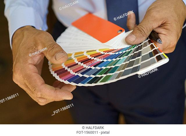 Midsection of businessman holding color swatches at office