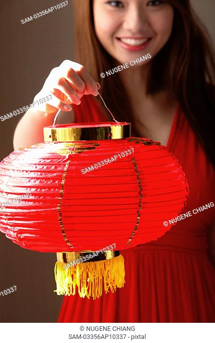Young woman holding red lantern and smiling