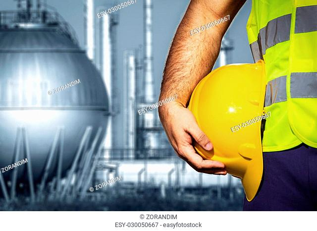 Hand or arm of engineer hold yellow plastic helmet in front of oil refinery industry