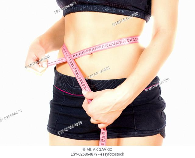 Slim Female with perfect healthy fitness body, measuring her thin waist with a tape measure. Caucasian young woman in sportswear, over white background