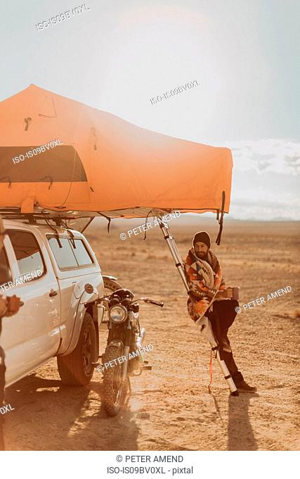 Motorcyclist beside tent admiring bike, Trona Pinnacles, California, US