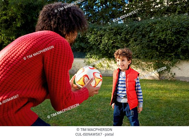 Father and son playing with football in garden smiling