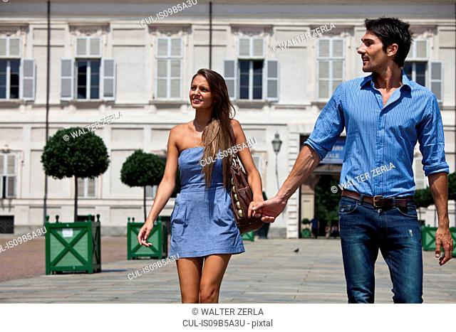 Young couple walking outdoors, hand in hand, Turin, Piedmont, Italy