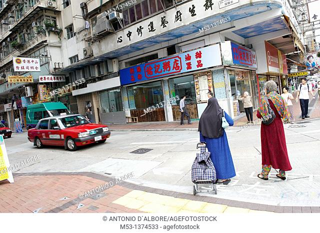 Two muslim woman walking along Jordan Road in the point crossing Wai Ching Street in Jordan district. Hong Kong. China