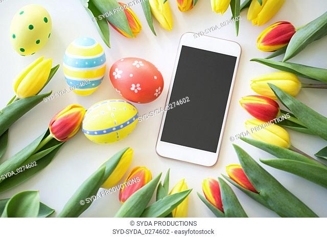 smartphone with easter eggs and tulip flowers