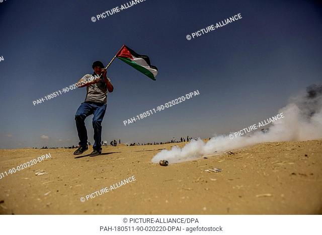 dpatop - A Palestinian protester holds a national flag as he takes cover Israeli tear gas during clashes with Israeli security forces along the Israel-Gaza...