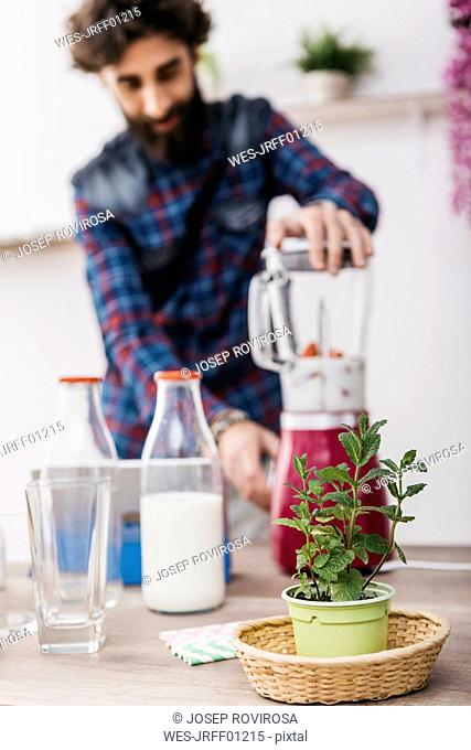 Man preparing smoothies with fresh fruits and vegetables at home