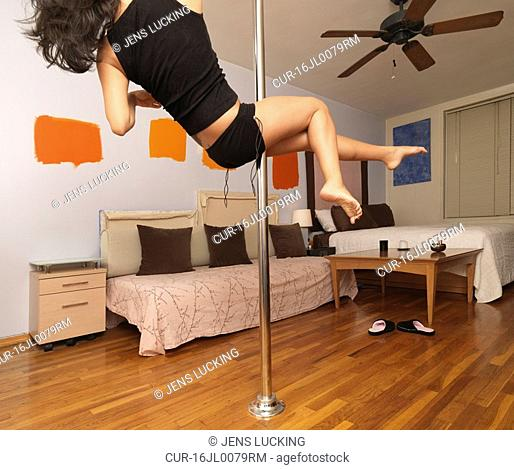 Woman spinning on pole in apartment