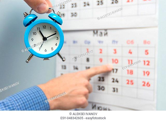 A hand holds a small alarm clock, in the background a hand points to long weekends and holidays on a wall calendar