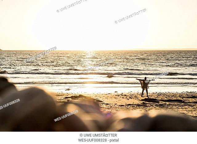 France, Crozon peninsula, woman standing on beach at sunset, arms outstretched