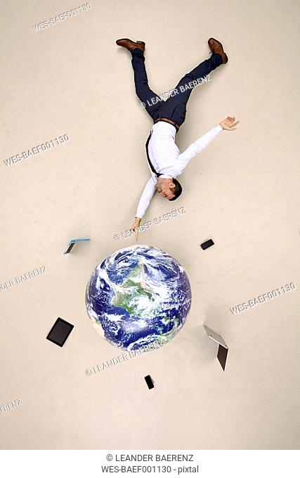 Businessman balancing globe with mobile devices on fingertip
