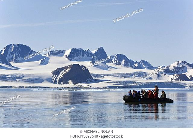 Zodiac cruisers get a view of the tidewater glacier in Isbukta Ice Bay on the western side of Spitsbergen Island in the Svalbard Archipelago, Barents Sea