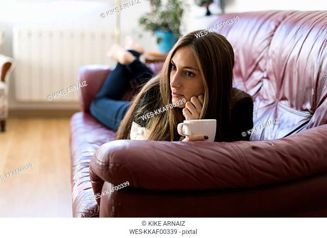 Young woman lying on couch holding cup of coffee