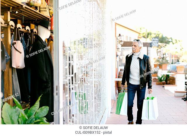 Senior man outside clothes shop, Livorno, Italy