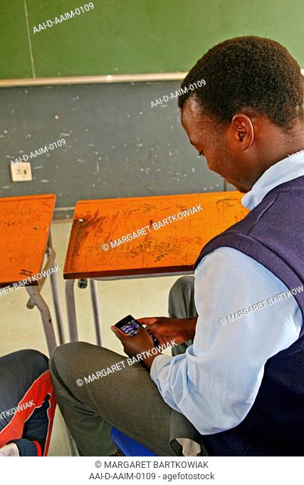 School boy on his cellphone in class, St Mark's School, Mbabane, Hhohho, Kingdom of Swaziland