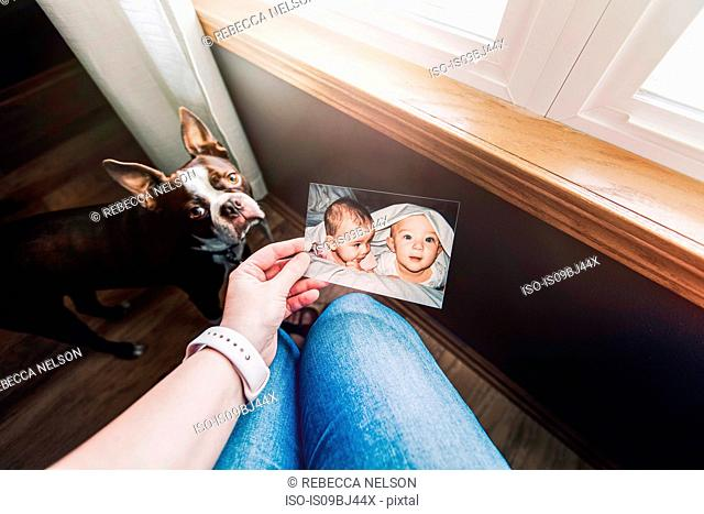 Mother holding photograph of twin baby girl and boy, personal perspective