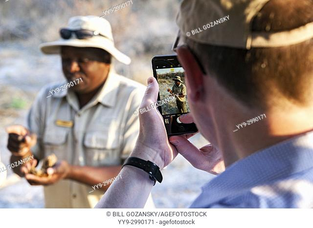 Man taking cell phone picture of guide on Sundowner Game Drive in Onguma Game Reserve, Namibia, Africa