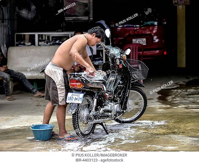 Man washes his moped, Phnom Penh, Cambodia
