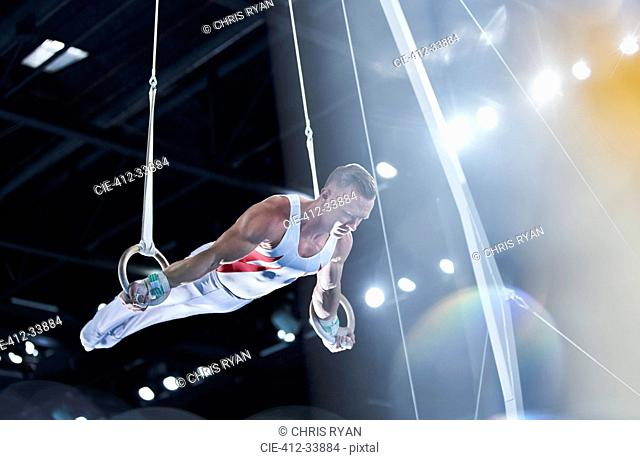 Male gymnast performing on gymnastics rings in arena