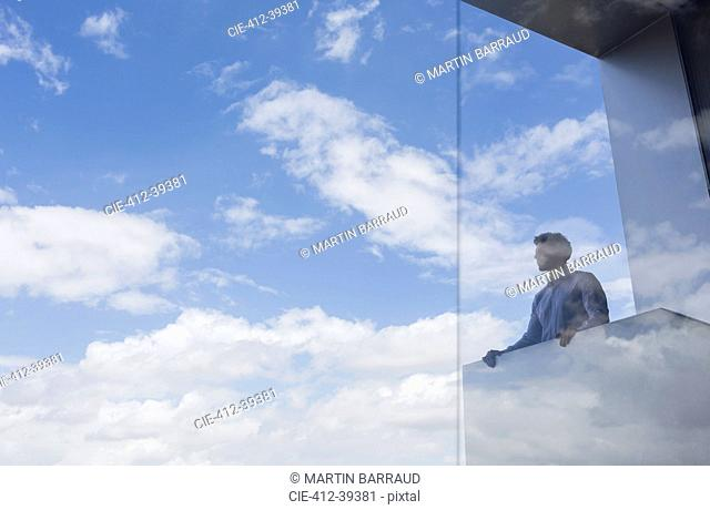 Pensive businessman standing at modern balcony looking at sunny blue sky and clouds